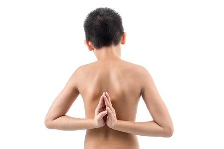 mottled background: young boy doing yoga exercise in Virasana or Hero Pose with reversed prayer or namaste in studio against a mottled background from behind