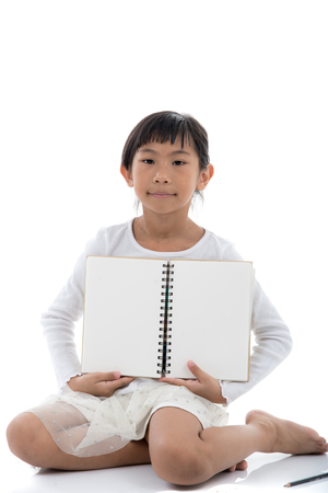 kid book: Asian girl sitting and holding blank notebook on white background.