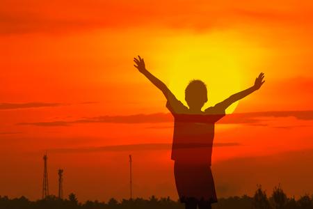 raising cans: Boy raising his hands standing during sun set Stock Photo
