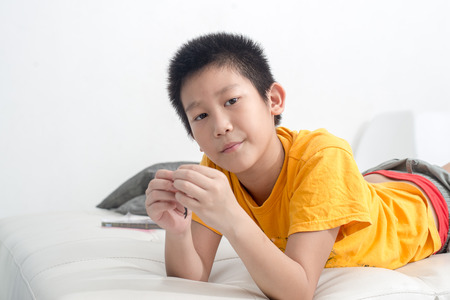 playdoh: Asian boy playing clay on sofa at home. Stock Photo