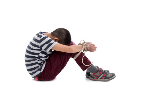 kidnapped: Missing kidnapped, abused, hostage, victim boy with hands tied up with rope in emotional stress and pain, afraid, restricted, trapped, call for help, struggle, terrified,