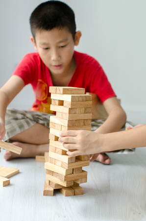 establishes: Asian children playing wooden blocks at home.