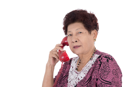 landline phone: portrait of a happy senior woman talking on telephone over white background Stock Photo