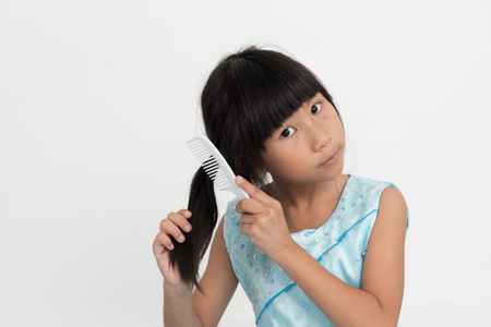 unruly: Asian girl brushing her hair on gray background.