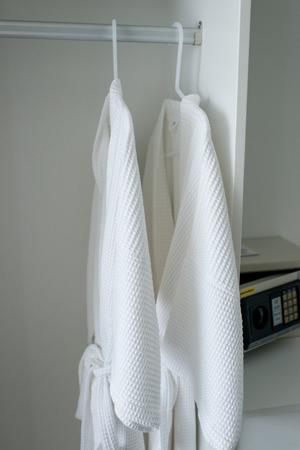 housecoat: Hanging white robes in room
