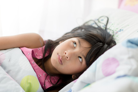 naptime: Cute Asian girl relaxing on bed at home with copyspace and looking up..
