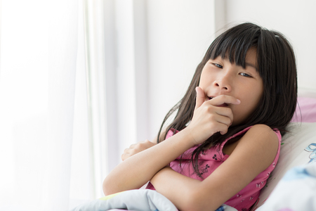 naptime: Cute Asian girl relaxing on bed at home with copyspace. Stock Photo