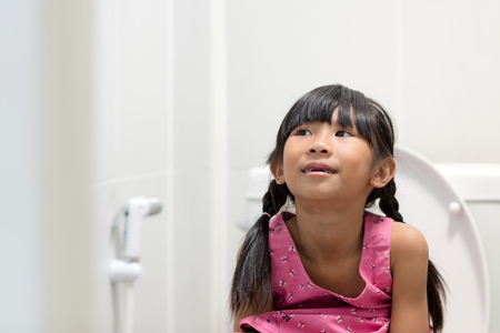 Asian girl sitting on toilet