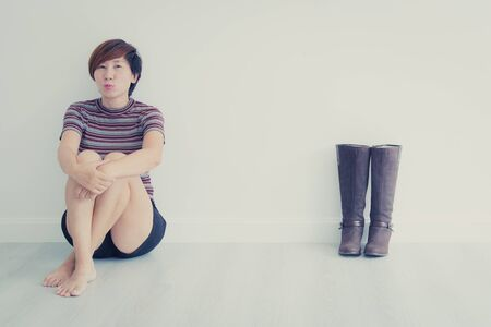 boot shoes: Smart Asian woman sitting with long boot shoes on gray floor, vintage tone Stock Photo