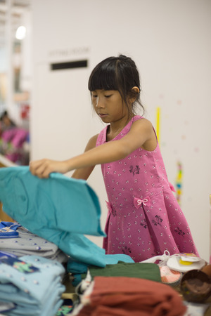 tries: Little girl chooses an outfit of a blouse and skirt in store of children clothing Stock Photo