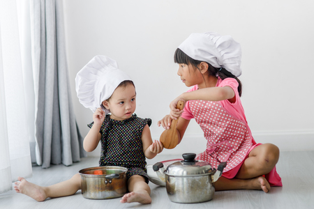 asian cook: Asian children playing  chef at home.