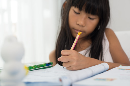 girl studying: cute Asian girl writing homework on a book at home, focused at pencil Stock Photo