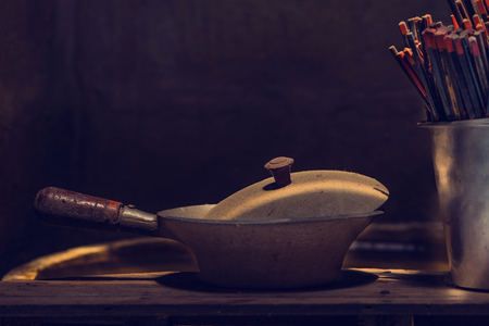 stove pipe: Dirty and dust baked pot with chopsticks for chinese style.  Still life with nature light. Stock Photo