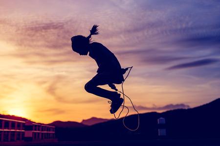 persona saltando: La muchacha que salta la cuerda en silueta con puesta de sol