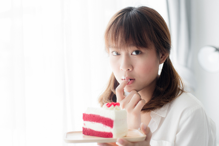 finger licking: Cute Asian teenager holding strawberry cake and licking her finger at home.