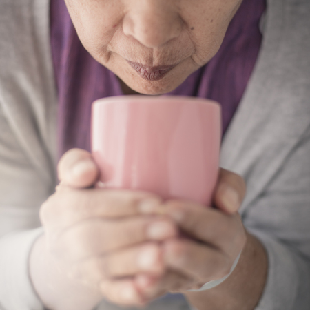 Old woman holding cup of hot coffee drink in her hands