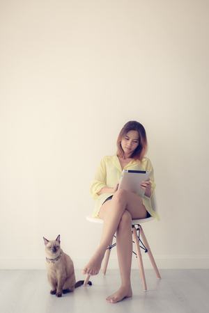 woman with tablet and beautiful cat in the living room photo
