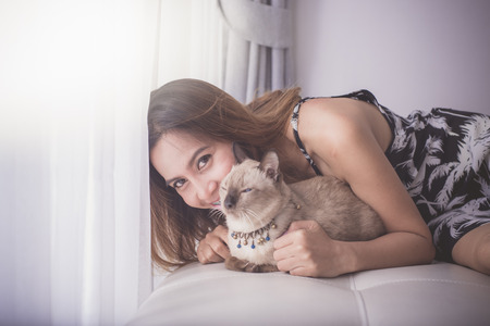 Asian woman and cat laying on sofa with window light. photo
