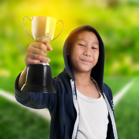 cut the competition: Happy boy in blue hood jacket holding trophy with soccer field background Stock Photo