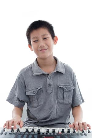Prodigy: Asian boy playing keyboard on white. Zdjęcie Seryjne