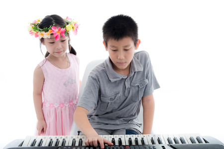 prodigy: Asian boy playing keyboard and dancer girl on white. Stock Photo