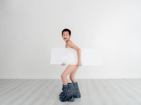 boy underwear: Asian shy boy with underwear holding blank white placard on gray background and copyspace.