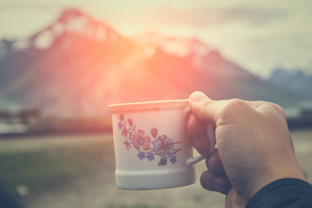 bodypart: Hand holding a cup of masala chia tea with warm light and Himalayan mountain background