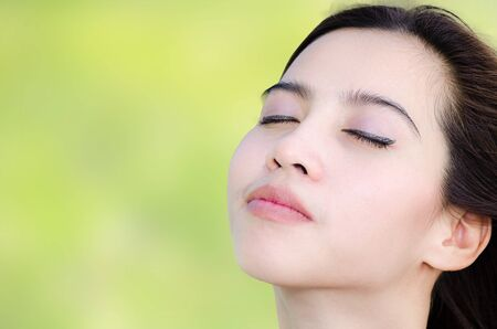 relaxing asian woman in the park, beautiful face photo