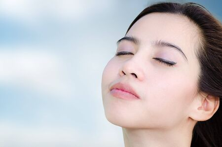 relaxing asian woman with sky background, beautiful face photo