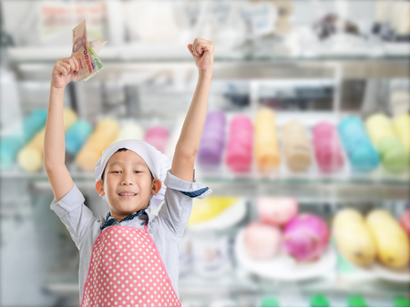 bakery store: Happy Young chef showing Thai money with sweet candy bakery store window