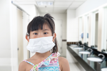 little girl standing in protective mask, white mask, bad smell public toilet Stock Photo