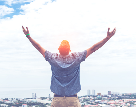 raise hand: Back of business man standing on the top of mountain, raise hand in vintage tone. Stock Photo