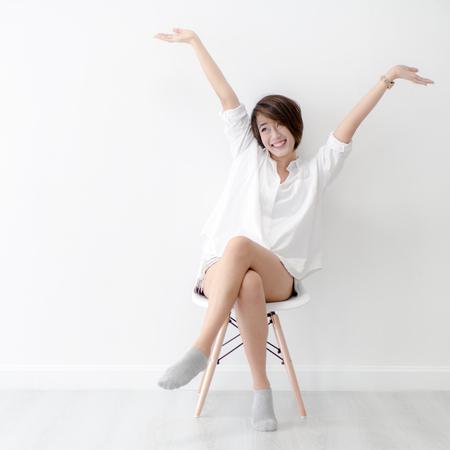 魅力的なアジアの女の子は白いモダンな上に座っている椅子し、家でくつろぐ。