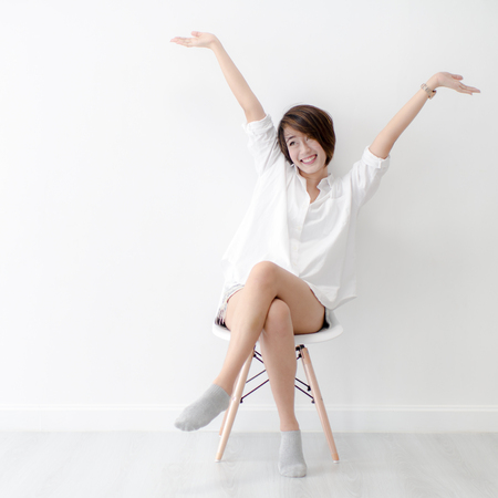 Attraktive asiatische Mädchen sitzen auf weißen modernen Stuhl und entspannen zu Hause.