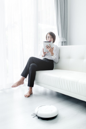 Modern life concept,  woman relaxing with tablet, automatic robotic hoover clean the room while