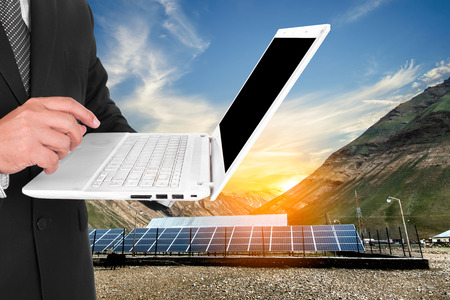 sun rise: Businessman holding laptop and standing by solar panels with sun rise, clipping path
