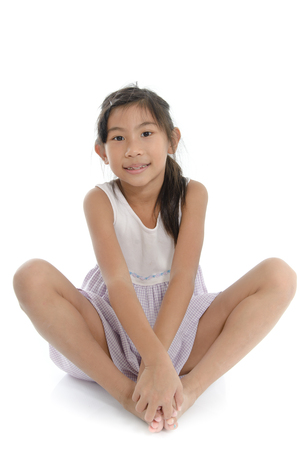 posting: Cute asian girl sitting on the floor, Isolated over white. Baddha Konasana yoga posting Stock Photo