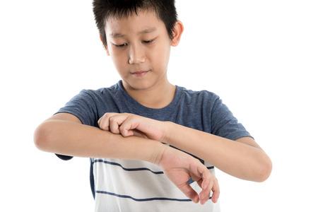 아시아 소년 흰색 배경에 그의 팔을 긁 적입니다. 선택적 초점