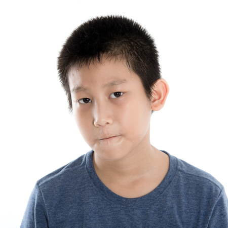 antagonistic: Head and Shoulders Close Up Portrait of Young Boy Wearing Blue T-Shirt and moody face on white. Stock Photo