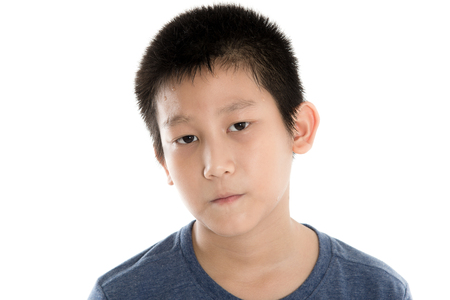 Head and Shoulders Close Up Portrait of Young Boy Wearing Blue T-Shirt and moody face on white. Banco de Imagens
