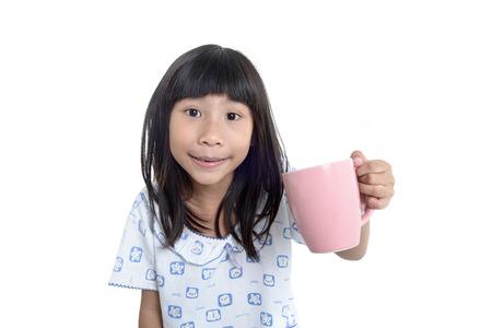 美しいヒスパニック系の女の子のパジャマを着て、白で隔離ミルクのカップを保持しています。 写真素材