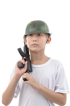 Asian boy with gun isolated on white background, childhood dreams concept