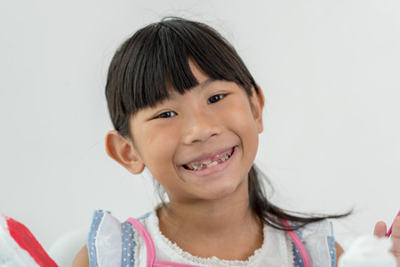 dientes sucios: Niño asiático sonriente durante las pinturas de los colores blancos juguetes muñeca de yeso en la tabla