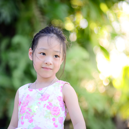 baby facial expressions: Happy Asian girl outdoor with bokeh background Stock Photo