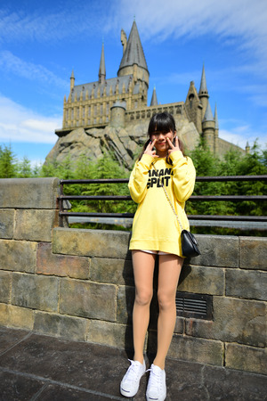 holiday blockbuster: OSAKA, JAPAN - OCTOBER 13, 2016: Japanese girl taking photo at The Hogwarts castle in The Wizarding World of Harry Potter in Universal Studio Osaka, Japan, was taken on October 13, 2016 Editorial