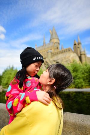 OSAKA, JAPAN - OCTOBER 13, 2016: Japanese girl holding her sister taking photo at The Hogwarts castle in The Wizarding World of Harry Potter in Universal Studio Osaka, Japan, was taken on October 13, 2016 Editorial