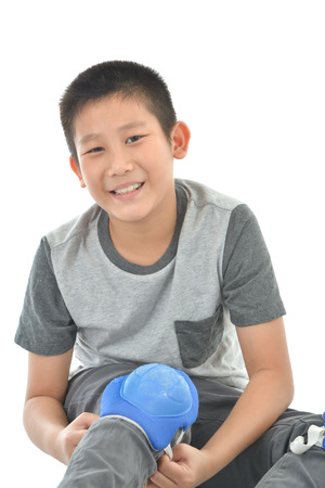 roller blade: Happy Asian boy wearing knee guard for playing roller blades on white. Stock Photo