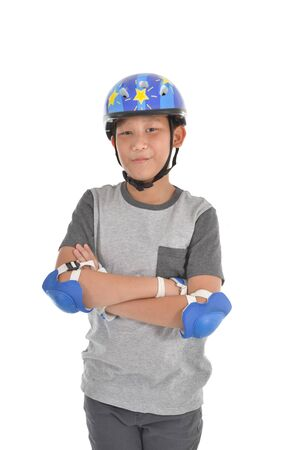 Happy Asian boy wearing safety guard for playing roller blades on white. Stock Photo