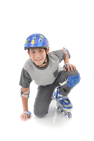 roller blade: Happy Asian boy wearing safety guard for playing roller blades on white. Stock Photo