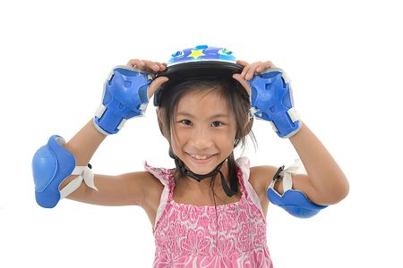 roller blade: Happy Asian girl wearing hand and headguard for playing roller blades on white. Stock Photo